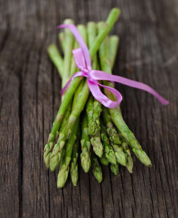 spears: Bunch of fresh green asparagus spears tied with ribbon on a rustic wooden table