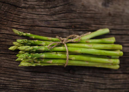 spears: Bunch of fresh green asparagus spears tied with string on a rustic wooden table