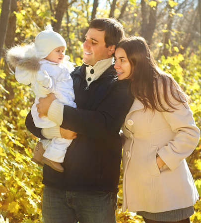 Young happy family with little daughter in autumn park Stock Photo - 14381547