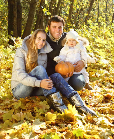 Young happy family with little daughter in autumn forest photo