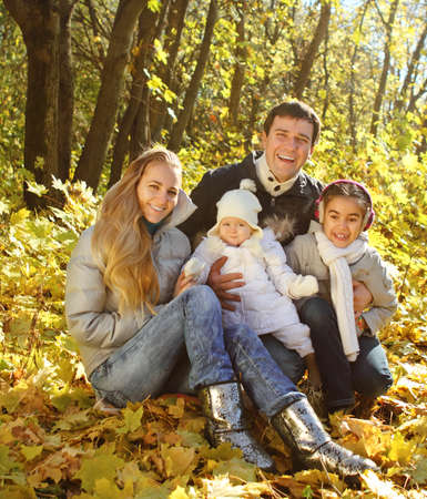Young happy family with two daughters in autumn forest photo