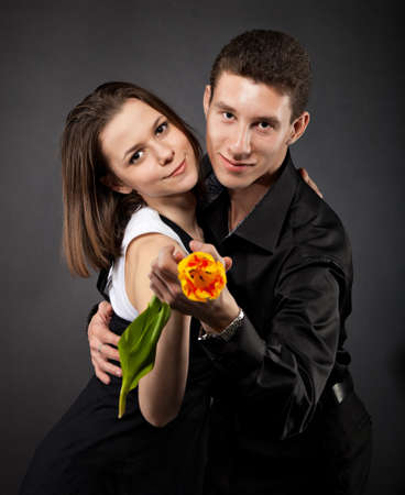 Portrait of a young funny couple in love with flower over dark background photo