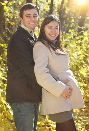 Happy smiling pregnant couple in the autumn forest photo