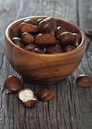 Roasted chestnuts in bowl on wooden background photo