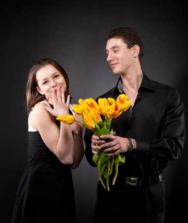 Portrait of a young funny couple in love with flowers over dark background Stock Photo - 14634229