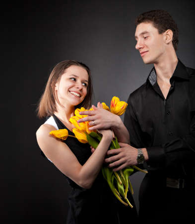 Portrait of a young funny couple in love with flowers over dark background Stock Photo - 14634230