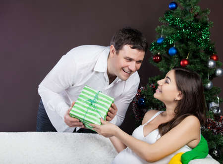 Happy pregnant couple with presents near the christmas tree Stock Photo - 15070363