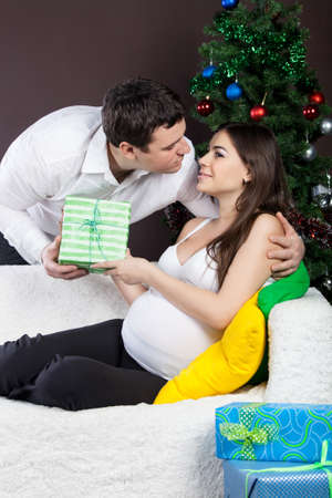 Happy pregnant couple with presents near the christmas tree  photo