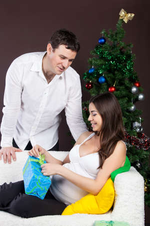 Happy pregnant couple with presents near the christmas tree  Stock Photo - 15070365