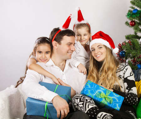 Happy family with Christmas presents near the Christmas tree photo