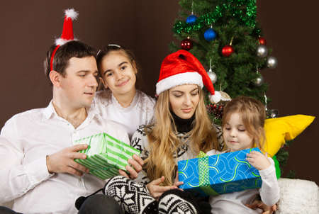Happy family opening Christmas presents near the Christmas tree Stock Photo - 15265323
