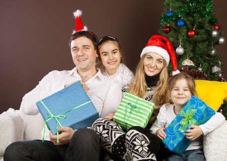 Happy family in Christmas hats near the Christmas tree Stock Photo - 15265327