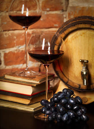 vino: Retro still life with red wine, books and barrel Stock Photo