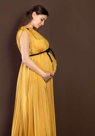 Happy pregnant woman in beautiful long dress touching her belly photo