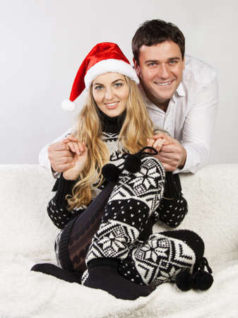 Portrait of a happy young couple wearing Christmas clothes photo