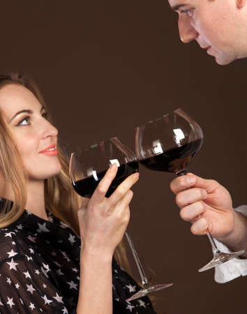 Young happy couple enjoying a glasses of red wine. Focus on glasses photo