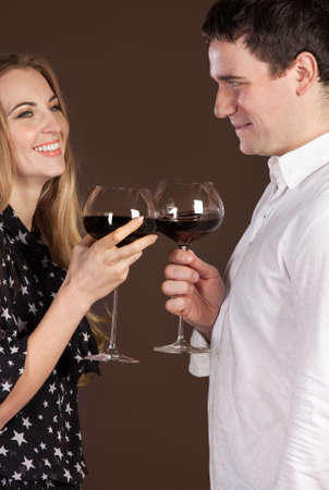 Young happy couple enjoying a glasses of red wine photo