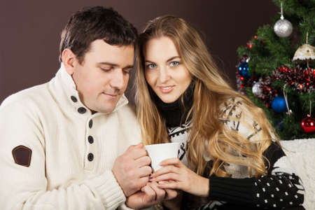 Portrait of a happy young couple near the Christmas tree photo
