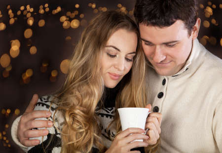 couple winter: Portrait of a happy young couple on blurred lights background  Stock Photo
