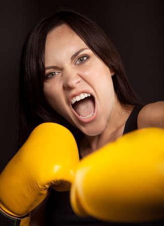 mujeres peleando: Retrato emocional de una niña en amarillo guantes de boxeo Foto de archivo
