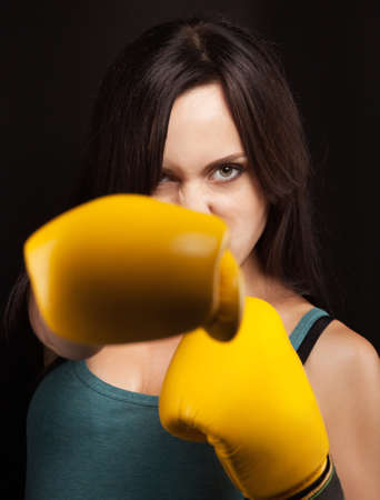Close up emotional portrait of a girl in yellow boxing gloves photo