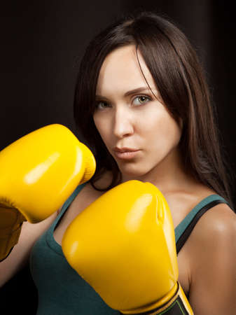 Emotional portrait of a girl in yellow boxing gloves photo