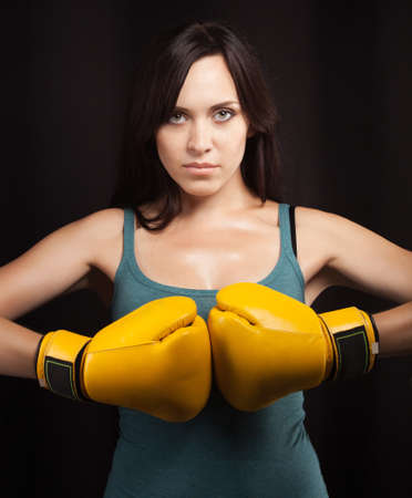 Portrait of a brunette girl in yellow boxing gloves photo