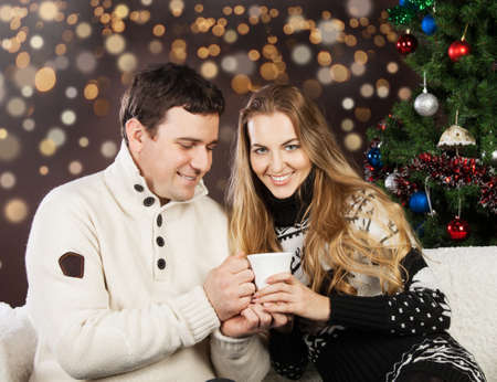 Portrait of a happy young couple on blurred lights background near the Christmas tree photo