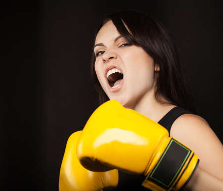 Portrait of a girl in yellow boxing gloves over dark background photo