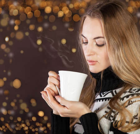 Beautiful blond young woman drinking coffee (or tea) photo
