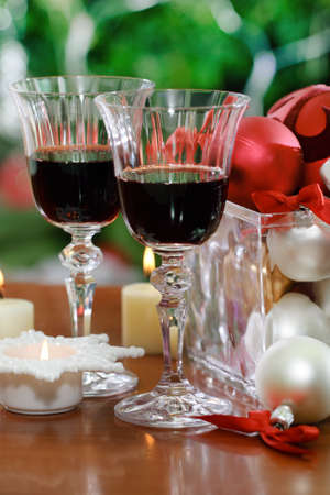 Glasses of red wine and Christmas decorations in front of Christmas tree for the holidays Stock Photo - 15400060