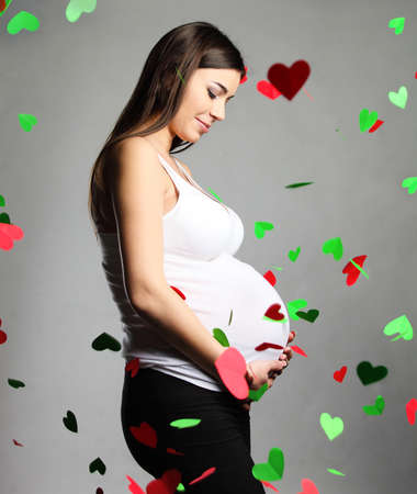 Happy pregnant woman touching her belly. Falling hearts around photo