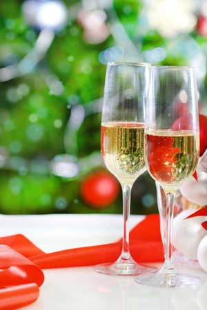 Glasses of champagne and Christmas decorations in front of Christmas tree for the holidays