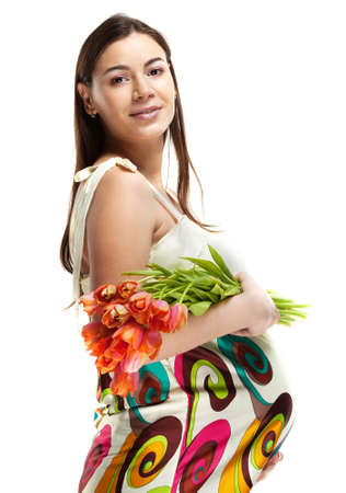 Happy young pregnant woman in bright dress holding flowers photo