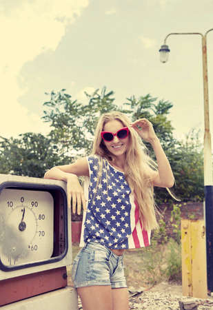 high price of oil: Blond girl holds hands on her glasses standing on damaged gas station Stock Photo