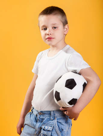Portrait of a little football fan boy on yellow background photo