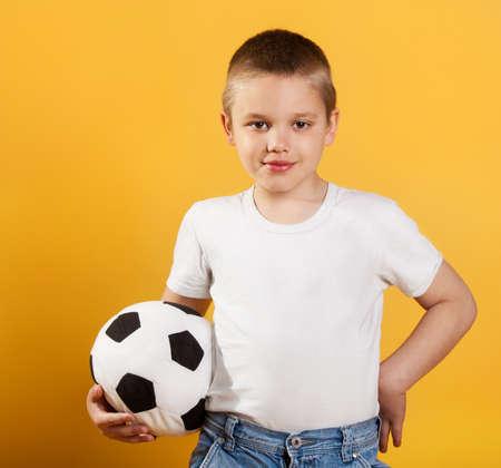 boy ball: Portrait of a little football fan boy on yellow background