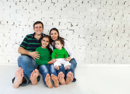 Portrait of a happy smiling family near white brick wall Stock Photo