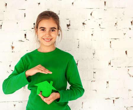 latin child: Little smiling brunette girl holding green house in hands. Concept