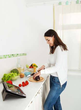 Portrait of a happy young woman preparing food in the kitchen photo