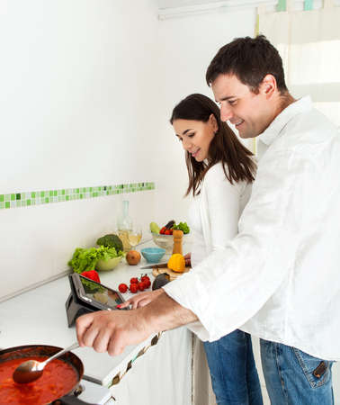 Portrait of a happy couple preparing food in the kitchen Stock Photo - 16250021