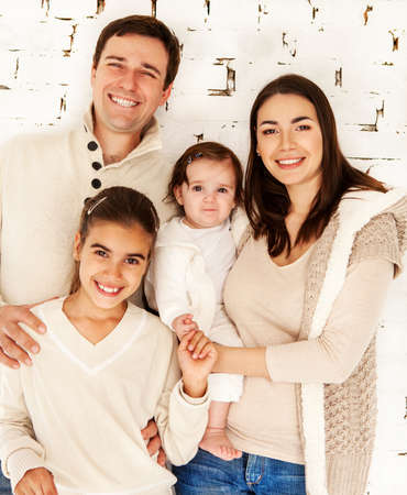 Portrait of a happy smiling family near white brick wall  photo