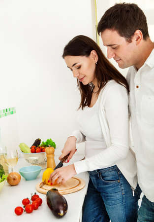 Portrait of a happy couple preparing food in the kitchen photo