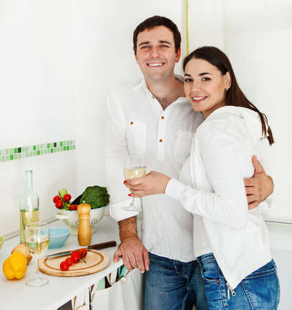 Portrait of a happy couple preparing food and drinking white wine in the kitchen photo