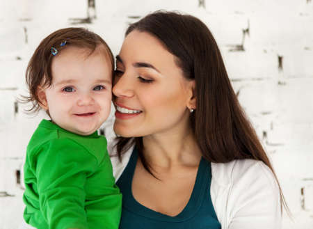 Happy smiling mother with eight months old baby near white brick wall photo