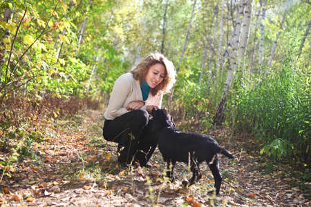 Young woman plaing with black labrador retriever puppy in the autumn forest Stock Photo - 16444058