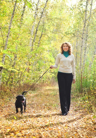 Young woman walking with black labrador retriever puppy in the autumn forest photo