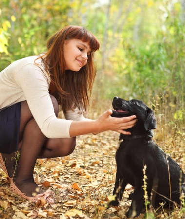 Teenager girl with black labrador retriever puppy outdoors Stock Photo - 16472491
