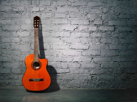 Acoustic guitar leaning on grungy gray brick wall photo