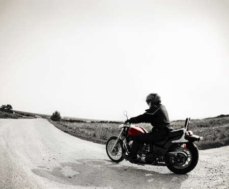 Biker on the country road against the sky photo
